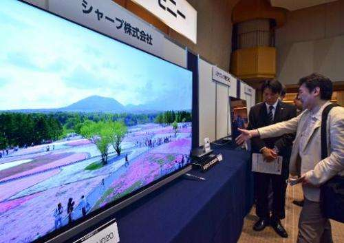 Visitors inspect Japanese electronics maker Sharp's new 4K television and newly developed 4K capable tuner, shown at the launch