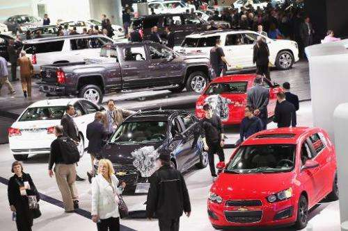 Visitors look over cars at the North American International Auto Show on January 14, 2014 in Detroit, Michigan