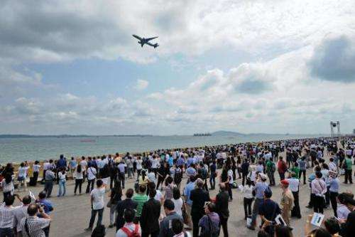 Visitors watch as an Airbus A350 flies past, during the Singapore Airshow, on February 12, 2014