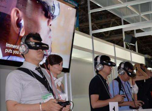 Visitors wear Japanese electronics giant Sony's new head mount display (HMD) 'HMZ-T3' to play videogames at the Tokyo Game Show