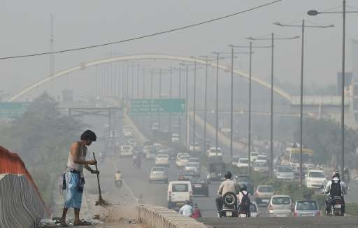 An Indian sweeper cleans a flyover as smog covers the New Delhi skyline