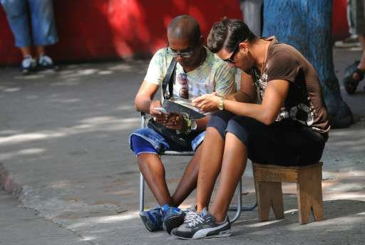 Cubans use their mobile devices to connect to the Internet via wifi in a street in Havana, on July 2, 2015