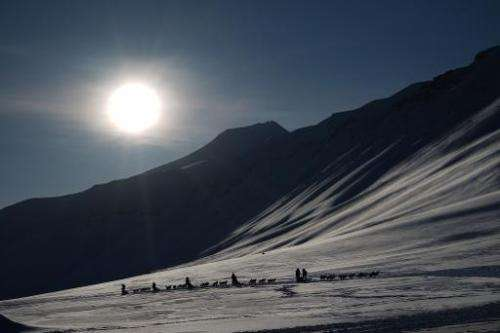 Eclipse watching tourists ride dog sleds outside of Longyearbyen, Svalbard, an archipeligo administered by Norway ahead of the M