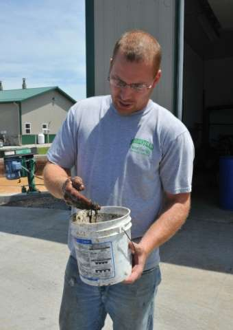 Farmer Ryan Rogers shows the rich fertilizer which comes out of an anaerobic digester used to treat manure at Homestead Dairy in