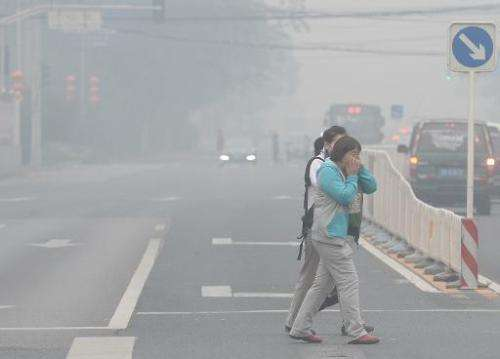 Pedestrians cover their faces as they cross a street in Beijing amid heavy smog on October 8, 2014