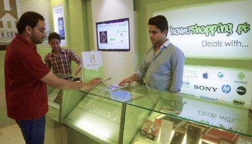 Shayaan Tahir (R), CEO of Homeshopping.pk, speaks to a customer at his call centre in Karachi