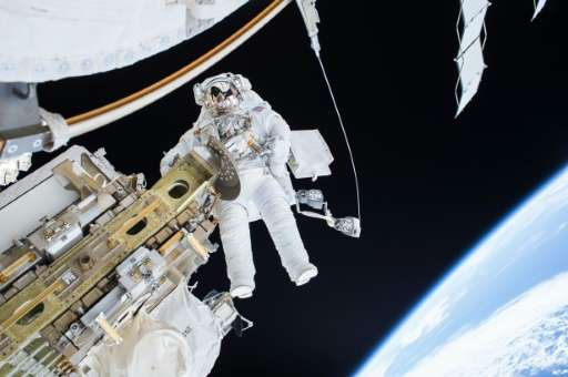 US astronaut Tim Kopra on a spacewalk to repair the International Space Station's mobile transporter rail car on December 22, 20