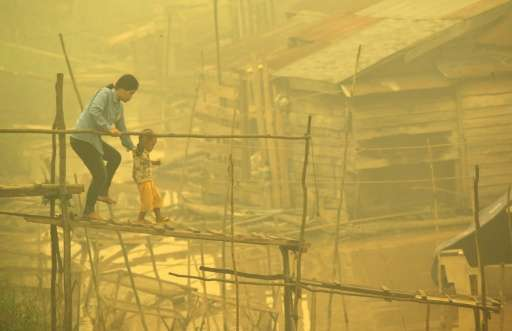 An Indonesian woman and a child walk on a bamboo bridge as thick yellow haze shrouds the city in Palangkaraya on October 22, 201