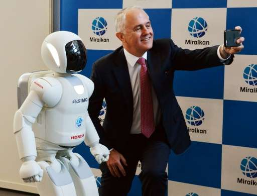 Australian Prime Minister Malcolm Turnbull takes a selfie with Honda Motor's humanoid robot Asimo at the National Museum of Emer