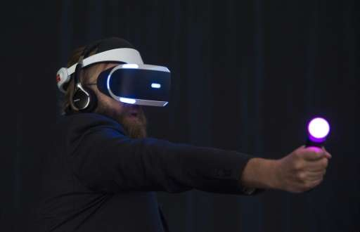 A visitor tries Sony's Project Morpheus virtual reality headset for PlayStation 4 in the Sony booth at the IFA electronics on Se