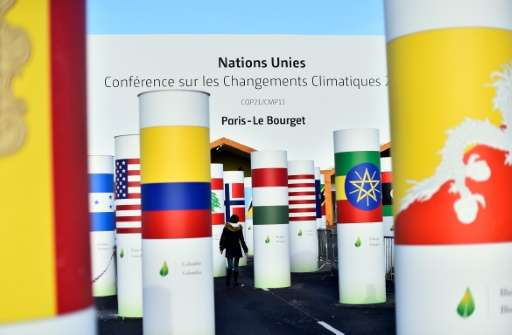 A woman walks past pillars with the  national flags of countries attending the COP 21 UN climate conference, in Le Bourget, nort