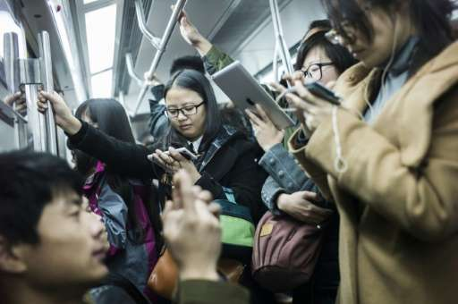 People use their phones in the metro during the morning rush hour in Beijing on November 17, 2014
