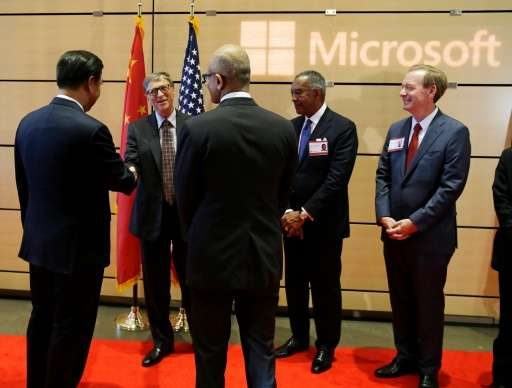 Chinese President Xi Jinping, left, shakes hands with Microsoft founder Bill Gates, second from left, as company CEO Satya Nadel