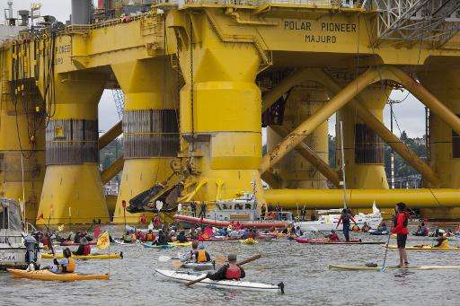 Greenpeace activists paddling in kayaks form a blockade to keep a mammoth Shell oil rig from departing from Seattle on a mission