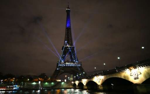 The Eiffel Tower is illuminated during the first day of the United Nations climate conference in Paris on November 30, 2015