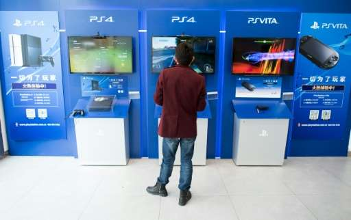 This photo taken on March 19, 2015 shows a man playing with a Sony PlayStation 4 in a shop in downtown Shanghai