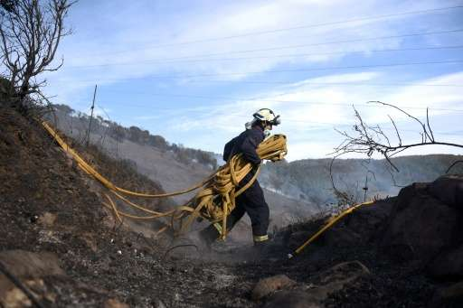 A firefighter carries works to put out wildfires near the northern Spanish Basque town of Berango on December 28, 2015