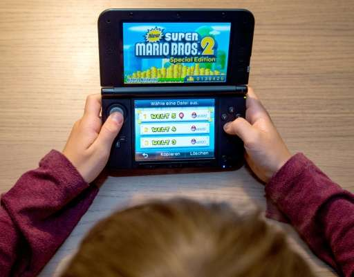 A boy plays 'Super Mario Bros. 2' on his Nintendo 3DS, in Sieversdorf, Germany