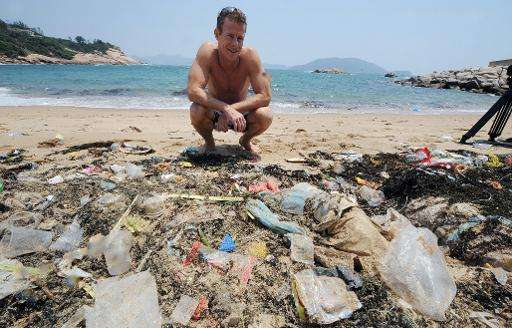 A conservationist looks at rubbish washed up on a beach on the south side of Hong Kong