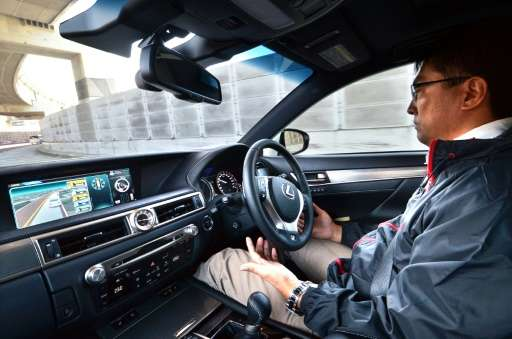 A driver tries out a Lexus GS450h on the Tokyo metropolitan highway during Toyota's advanced technology presentation