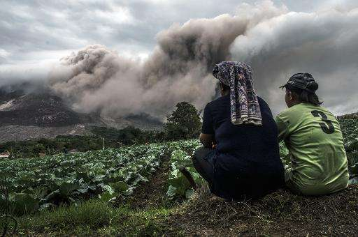 A farming family look on as Mount Sinabung volcano erupts in Karo district, North Sumatra province on June 16, 2015