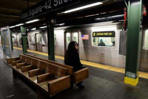 A lonely commuter waits to catch the train at a subway station in New York on January 26, 2015