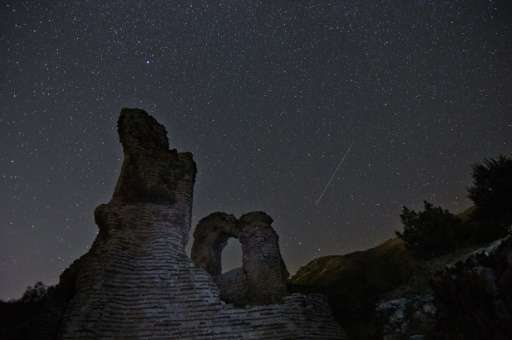 A long exposure image showing a Perseids meteor (R) streaking across the night sky near the town of Pirdop, August 12, 2015