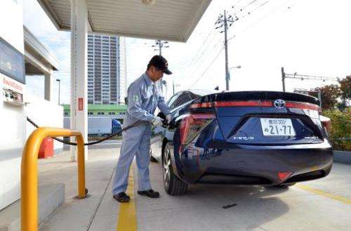 "A man refuels Toyota Motor's fuel cell vehicle ""Mirai"" at a hydrogen station in Tokyo on November 17, 2014"