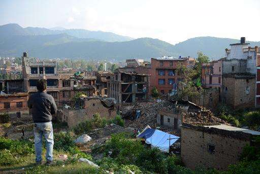 A man stands near collapsed houses in Bhaktapur, on the outskirts of Kathmandu, on April 27, 2015, two days after a 7.8 magnitud