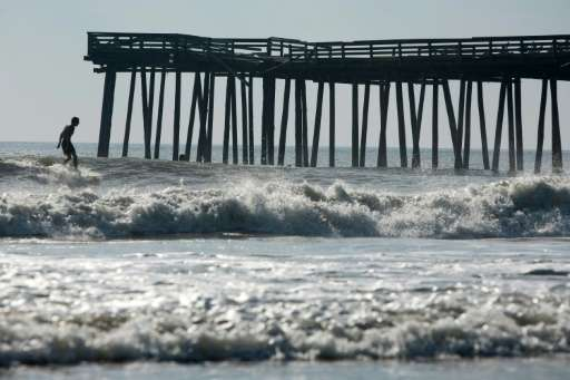 A man surfs near the Virginia Beach Fishing Pier, which suffered damage from Hurricane Irene, on August 28, 2011 in Virginia Bea