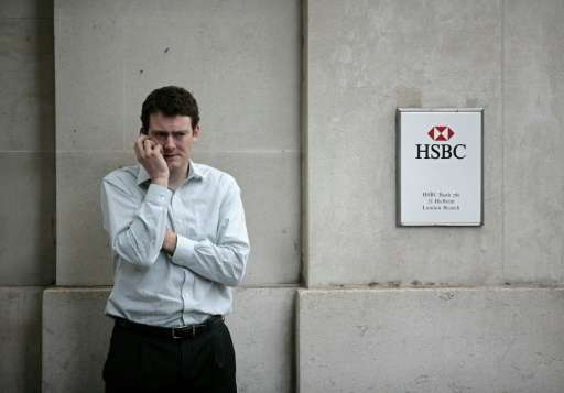 A man uses his mobile phone outside an HSBC bank branch in London