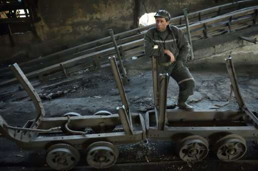A miner next to mining carriages as he waits for the last shift at the coal mine in the Romanian city of Petrila, on October 30,