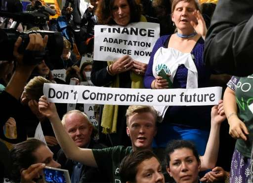 """An activist holds a banner reading """"Don't compromise our future"""" during the UN conference on climate change COP21 in L"""