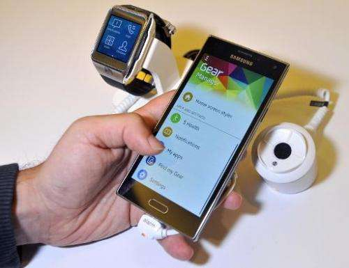 An employee demonstrates Samsung Z910F smartphone and the SM-R380 smartwatch, at the Tizen Developer Conference in San Francisco
