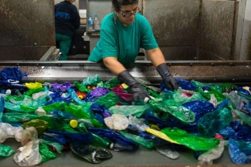 An employee sorts waste collected by fishermen at a plastic processing plant in Chiva, near Valencia in Spain