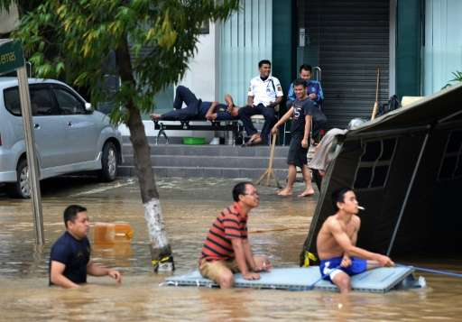 A new report says human-influenced climate change likely means more extreme weather events like the floods that hit Jakarta, Ind