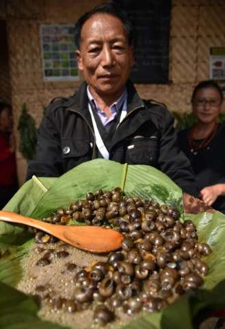 An Indian Naga shows a dish made of snails at The Indigenous Mei-Ramew Food Festival in Mawphlang in India's northeastern state