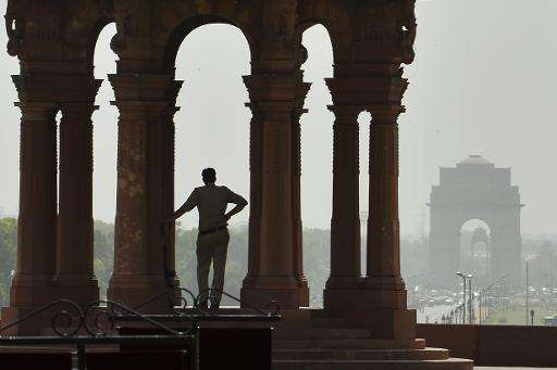 An Indian policeman stands in the shade at the Indian Defence Ministry in New Delhi on May 26, 2015