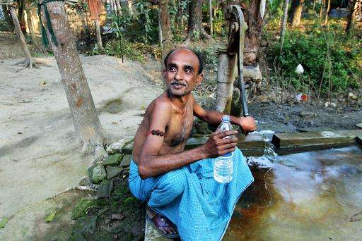 An Indian villager holds a bottle of drinking water distributed from Sulabh Safe Drinking Water Project