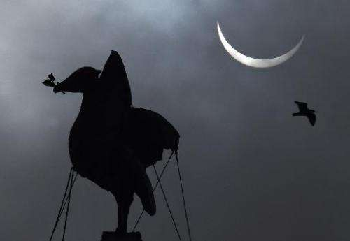 A partial solar eclipse is visible next to the iconic Liver Bird on top of the Liver Building in Liverpool, north-west England o