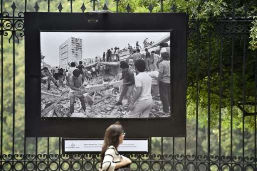 A pedestrian walks past a picture showing the damage caused by the 1985 earthquake, on a fence on Reforma avenue in September 17