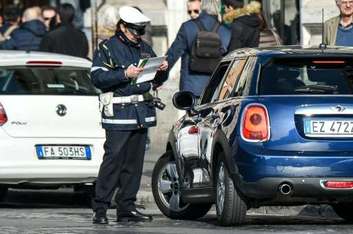 A police officer controls cars and scooters during the limited traffic day in centeral Rome on December 29, 2015