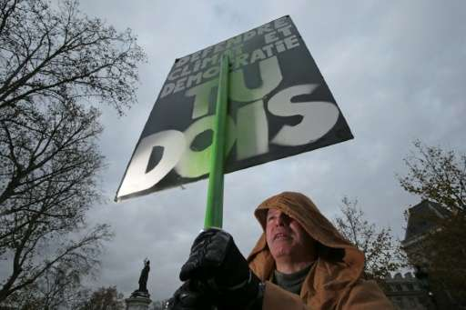 """A protestor dressed in reference to Star Wars holds stands in front of a sign reading """"Defend climate and democracy, you mu"""