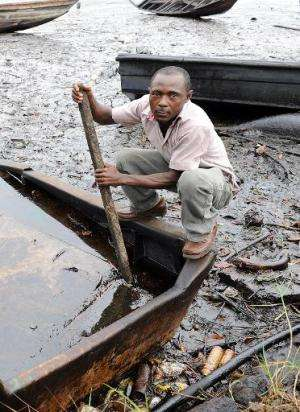 A resident of Bodo, Ogoniland region in Rivers State, tries to separate the crude oil from water in a boat with a stick, after t
