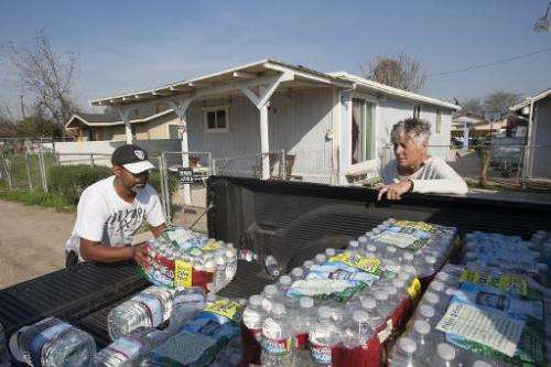 A resident of East Porterville, California, receives a delivery of drinking water as water wells supplying hundreds of residents