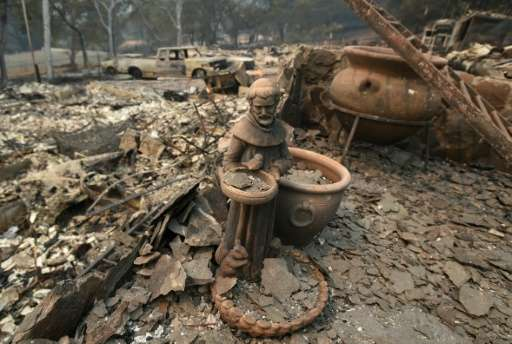 A statue is seen amidst rubble from a burned home during the Valley fire in Middletown, California on September 13, 2015