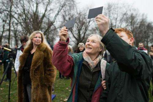 Astronomy enthusiasts look towards the sky from Regent's Park in central London ahead of the partial solar eclipse on March 20,