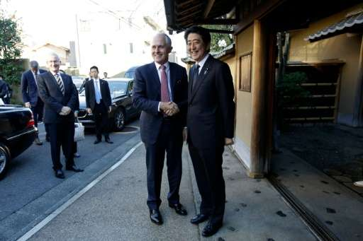 Australian PM Malcolm Turnbull (L) and Japanese PM Shinzo Abe (R) shake hands prior to a tea ceremony hosted Sen Soshitsu, the G