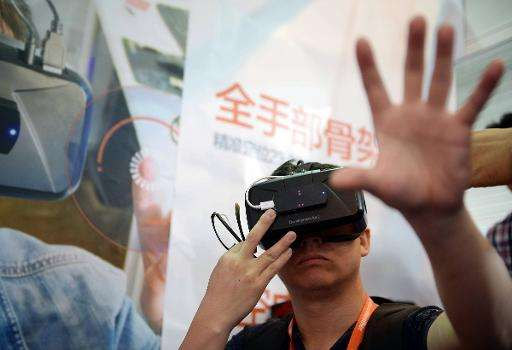 A visitor tries on virtual reality glasses from Oculus Rift Development Kit 2 during the first Consumer Electronics Show in Asia