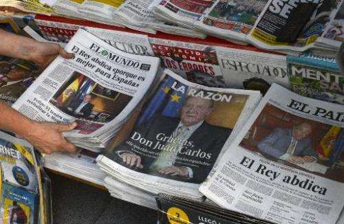 A woman arranges special editions of Spanish newspapers in Madrid on June 2, 2014 following the announcement by King Juan Carlos